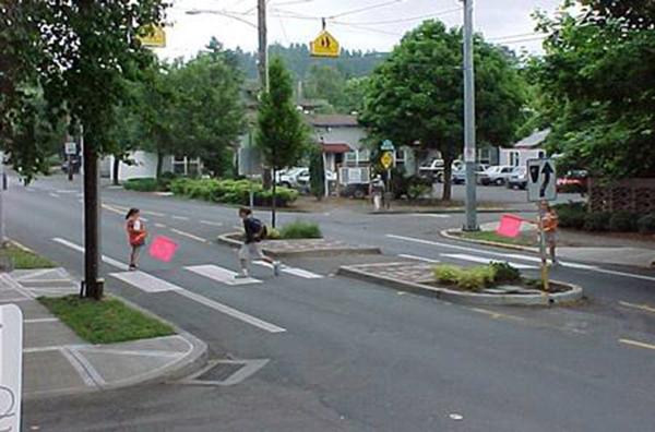 Agentes de trânsito sinalizam os pedestres que desejam atravessar com bandeiras de cor de alta visibilidade (laranja, amarelo, fucsia..)