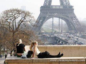 Mulheres descansam em mureta em frente à Torre Effeil, em dia ensolarado e poluído (14.03.2014)