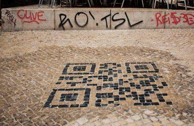 O símbolo desenhado na calçada portuguesa no Chiado para os turistas com smartphone terem informação rápida sobre a zona